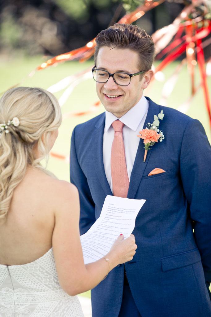 Bräutigam lächelt während dem Eheversprechen seiner Braut