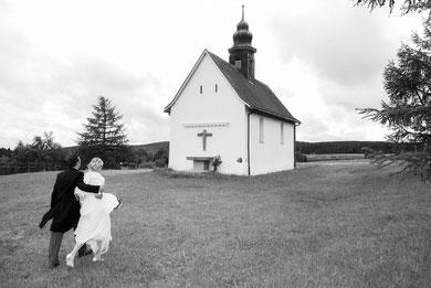 Brautpaar auf dem Weg zu kleiner Kapelle auf einem Hügel