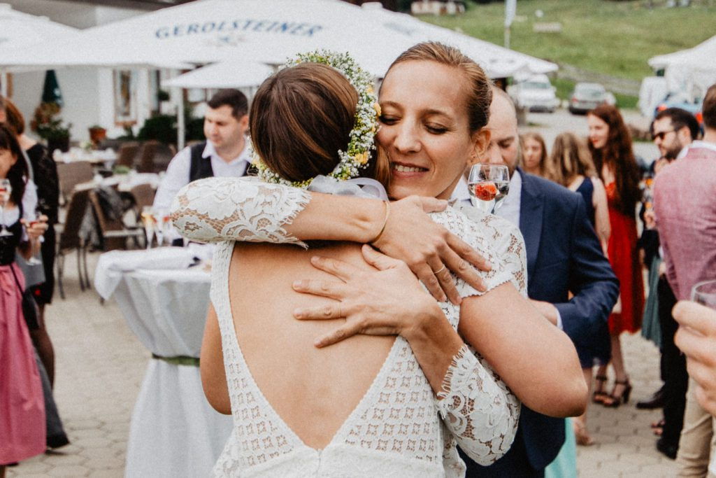 Eine glückliche Braut umarmt ihre Traurednerin von Strauß & Fliege