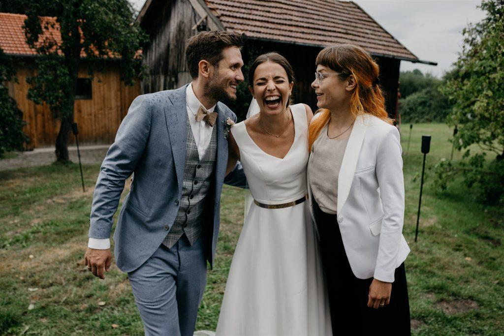Ein strahlendes Brautpaar mit Traurednerin Veronika Bracks von Strauß & Fliege