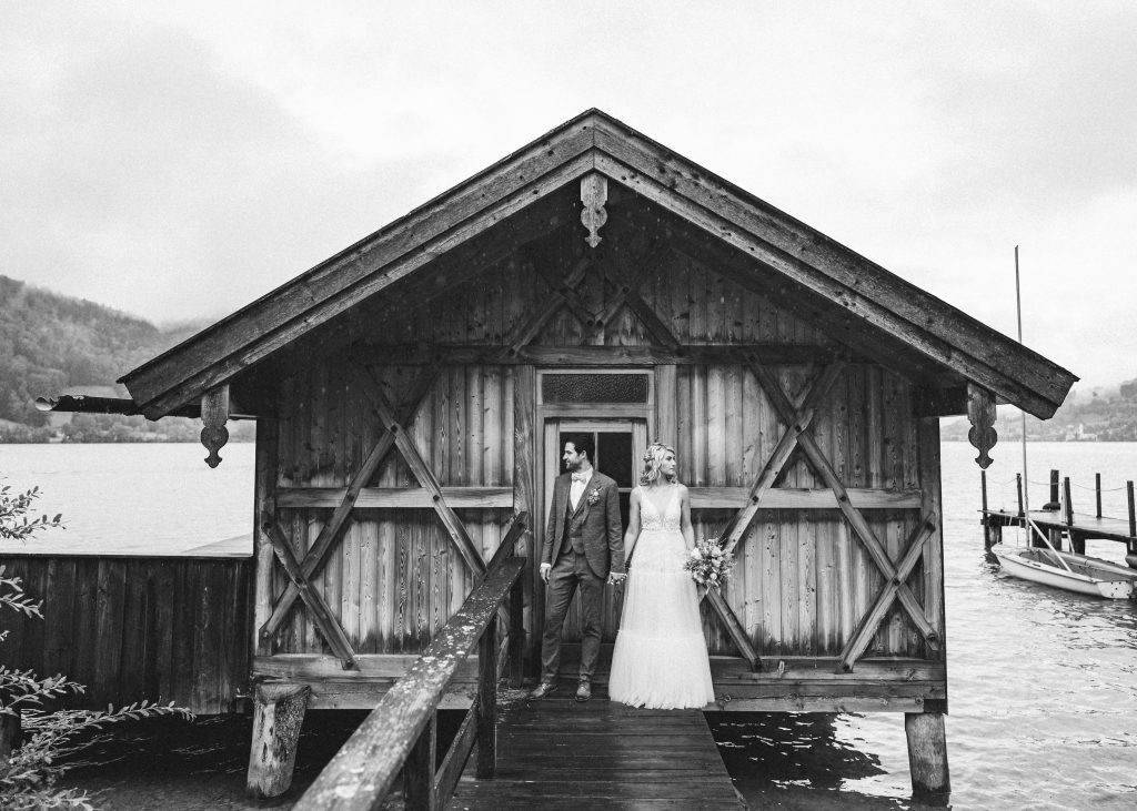 Brautpaar vor Holzhütte auf dem Steg am See