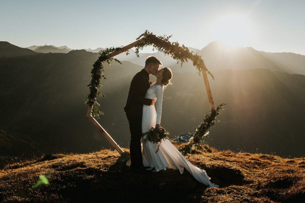 Brautpaar unter Blumenbogen auf einer Bergspitze mit Panoramablick