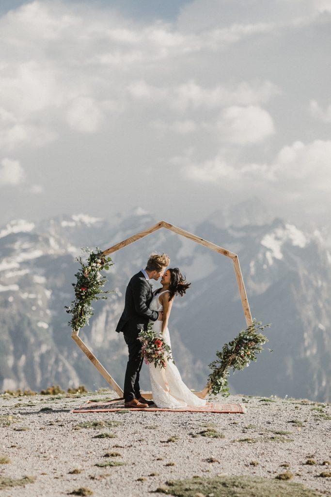 Elopement Brautpaar unter Blumenbogen auf einer Bergspitze mit Panoramablick