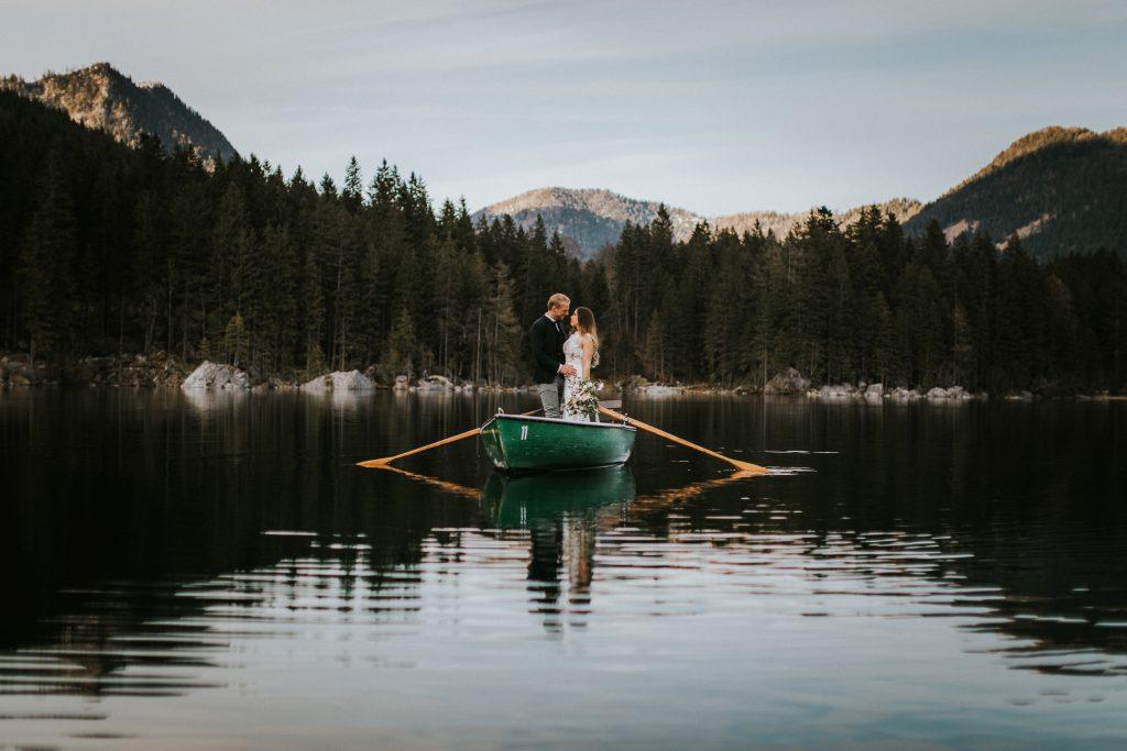 Brautpaar in Holzboot auf einem einsamen Gebirgssee