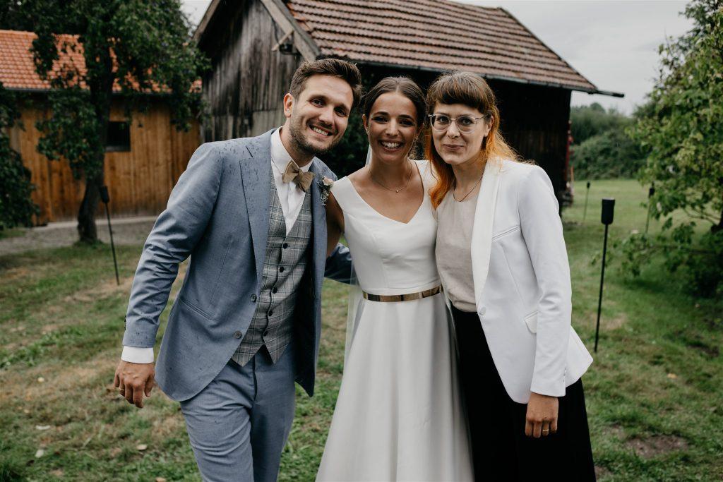 Strahlendes Brautpaar mit Traurednerin von Strauß & Fliege