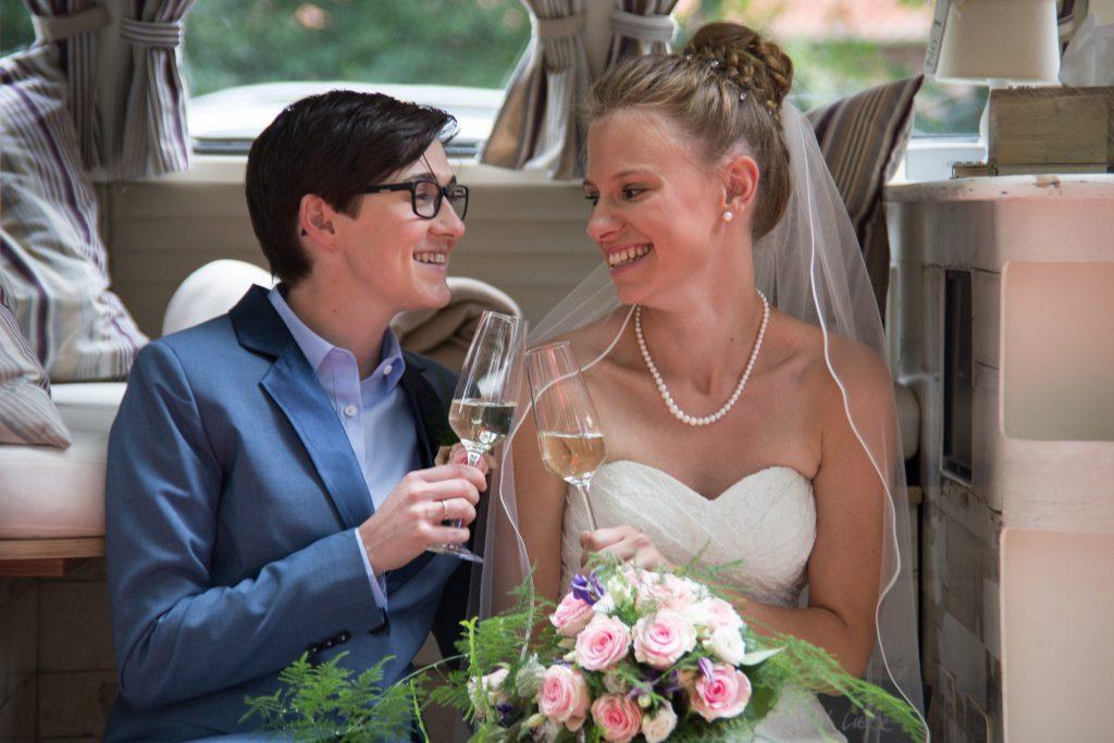 Ehe für Alle - Braut und Braut stoßen an auf Ihre Hochzeit