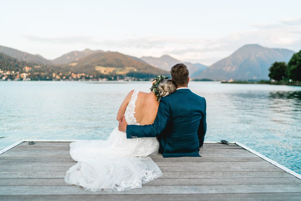 Glückliches Brautpaar umarmt sich auf einem Holzsteg am See