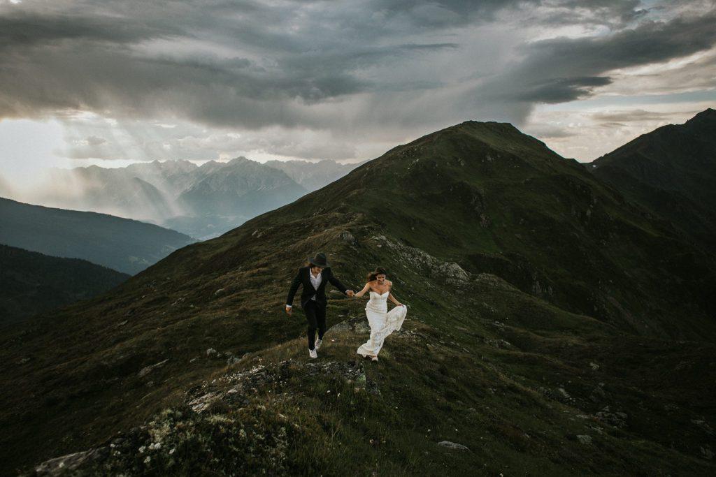 Elopement: Rennendes Brautpaar auf einer Bergspitze in den Alpen