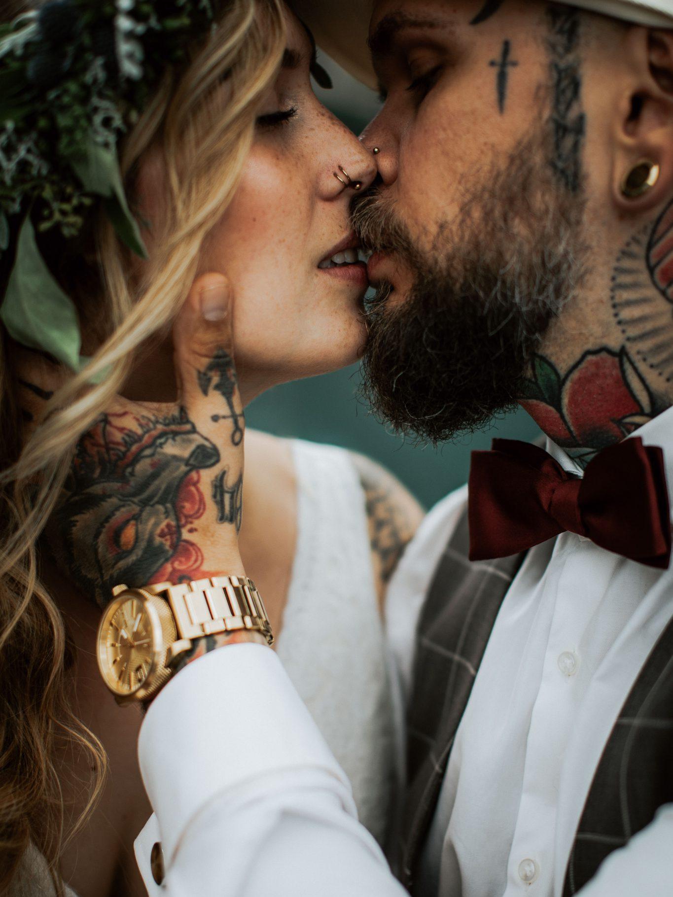 Tätowiertes Brautpaar küsst sich zärtlich