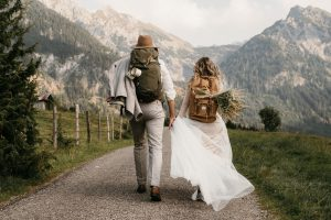 Brautpaar mit Wanderrucksäcken beim Spaziergang in den Bergen