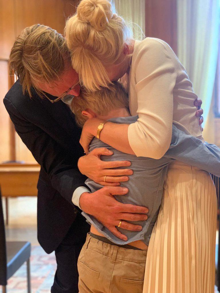 Glückliches Paar umarmt kleinen Sohn nach dem Ja-Wort auf dem Standesamt