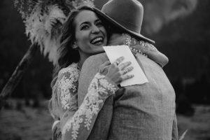 Strahlende Braut umarmt ihren Bräutigam nach dem Eheversprechen