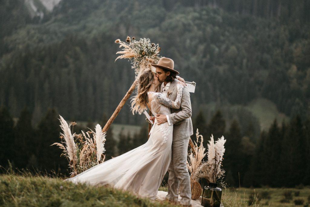 Strahlendes Brautpaar küsst sich nach der freien Trauzeremonie