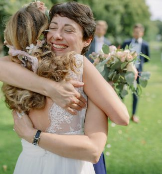 Glückliche Braut umarmt Traurednerin Carola vor Dankbarkeit und Freude