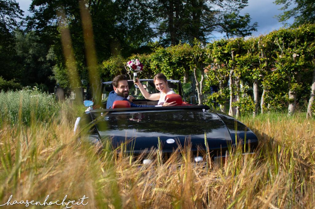 Brautpaar im Hochzeitswagen in einer Sommerwiese