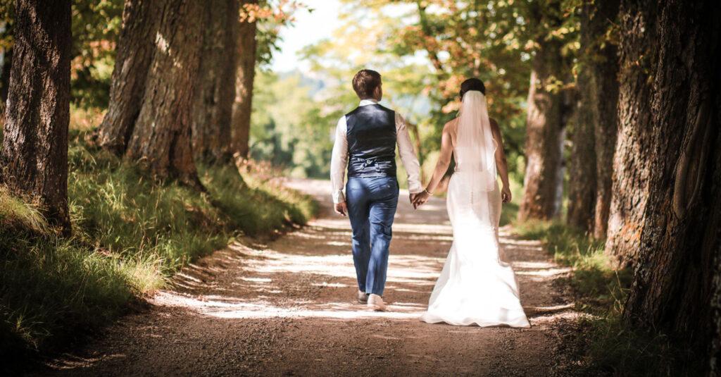 Brautpaar schlendert durch sonnendurchflutete Allee
