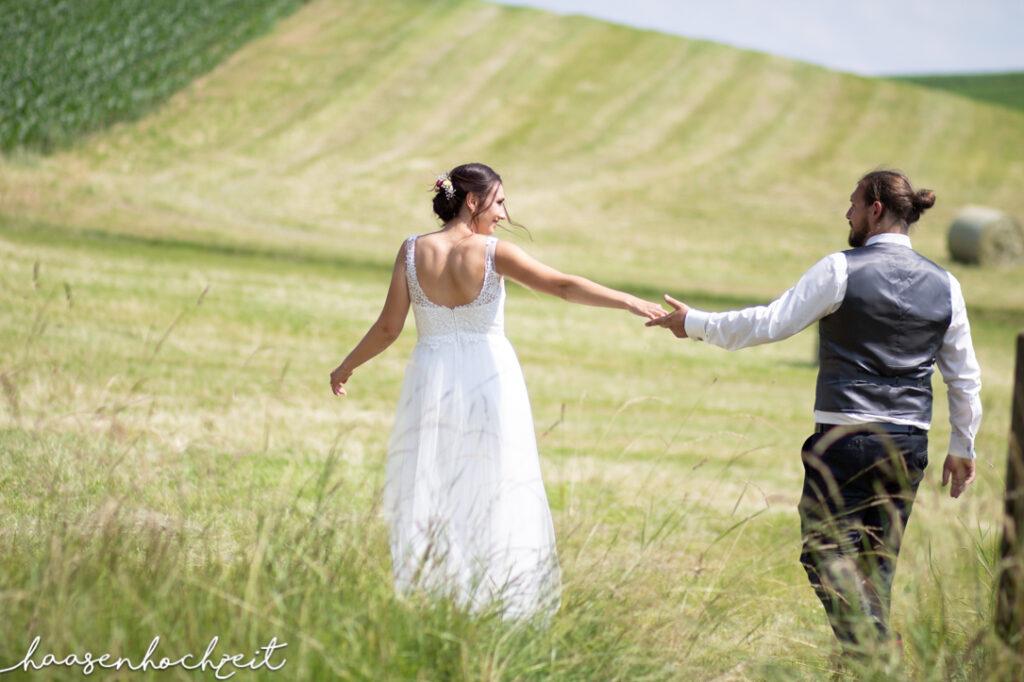 Brautpaar flaniert über Sommerwiese