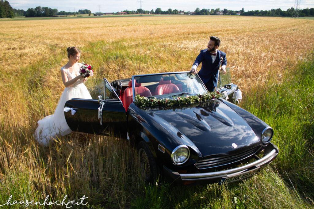 Oldtimer Cabrio als Brautauto in einer Sommerwiese