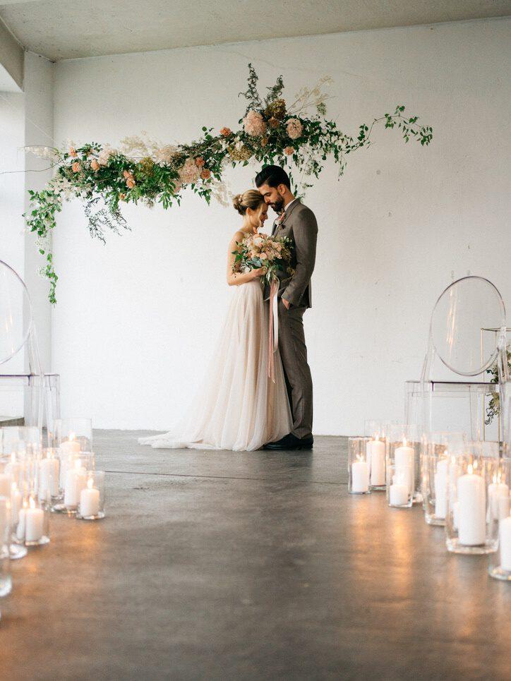 Brautpaar unter dem Traubogen im Kerzenschein