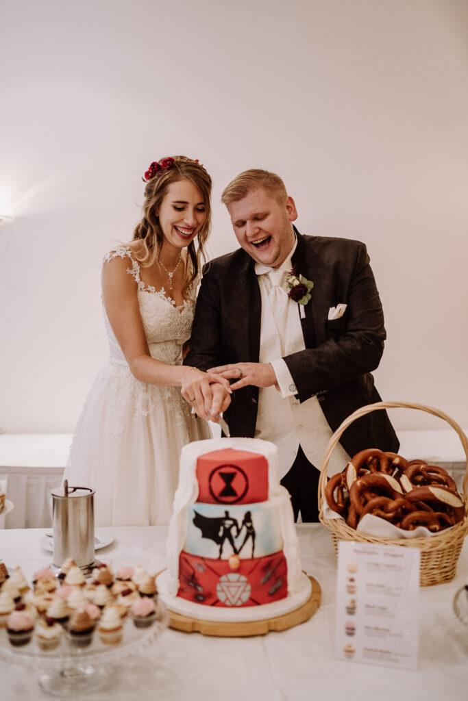 Lachendes Brautpaar schneidet Hochzeitstorte an