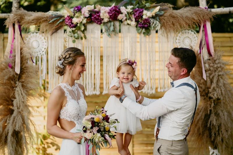 Strahlendes Brautpaar mit kleiner Tochter