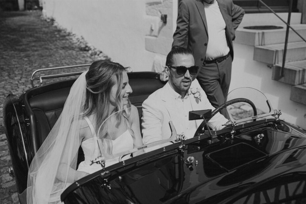 Braut und Bräutigam mit schickem Oldtimer als Brautwagen