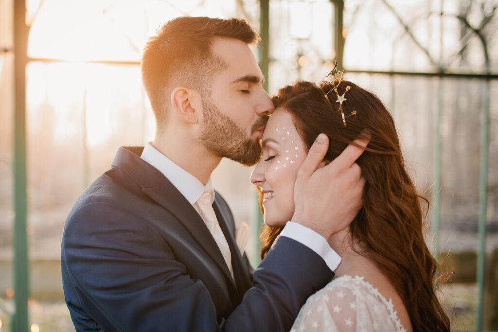Bräutigam küsst seine Braut zärtlich auf die Stirn