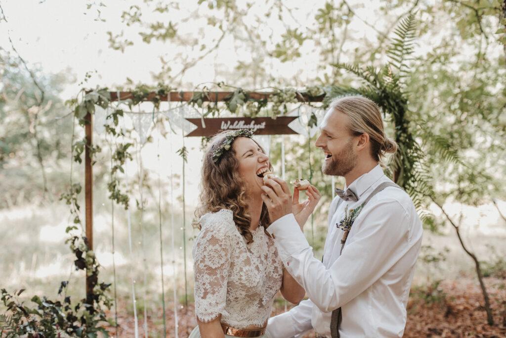 Lachendes Brautpaar füttert sich gegenseitig mit Hochzeitstorte
