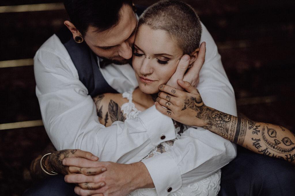 Tättowiertes Brautpaar umarmt sich innig