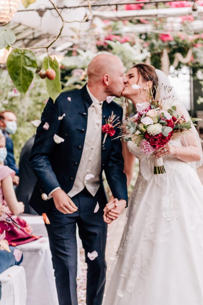 Brautpaar küsst sich nach der Trauzeremonie alte Gärtnerei München