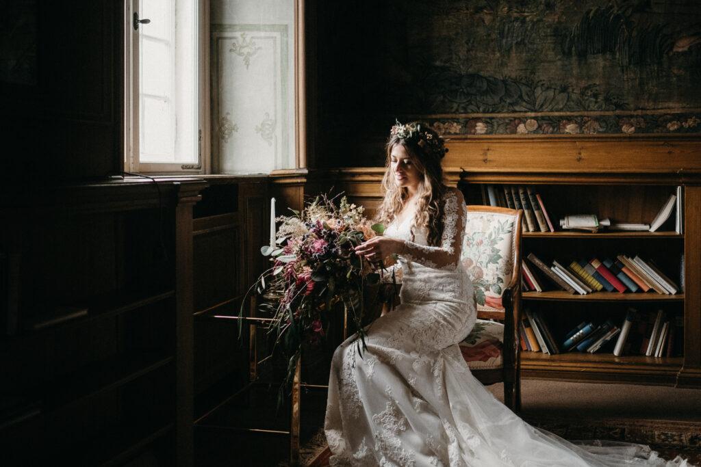 Boho Braut in moderner Spitze und wildem Blumenstrauß