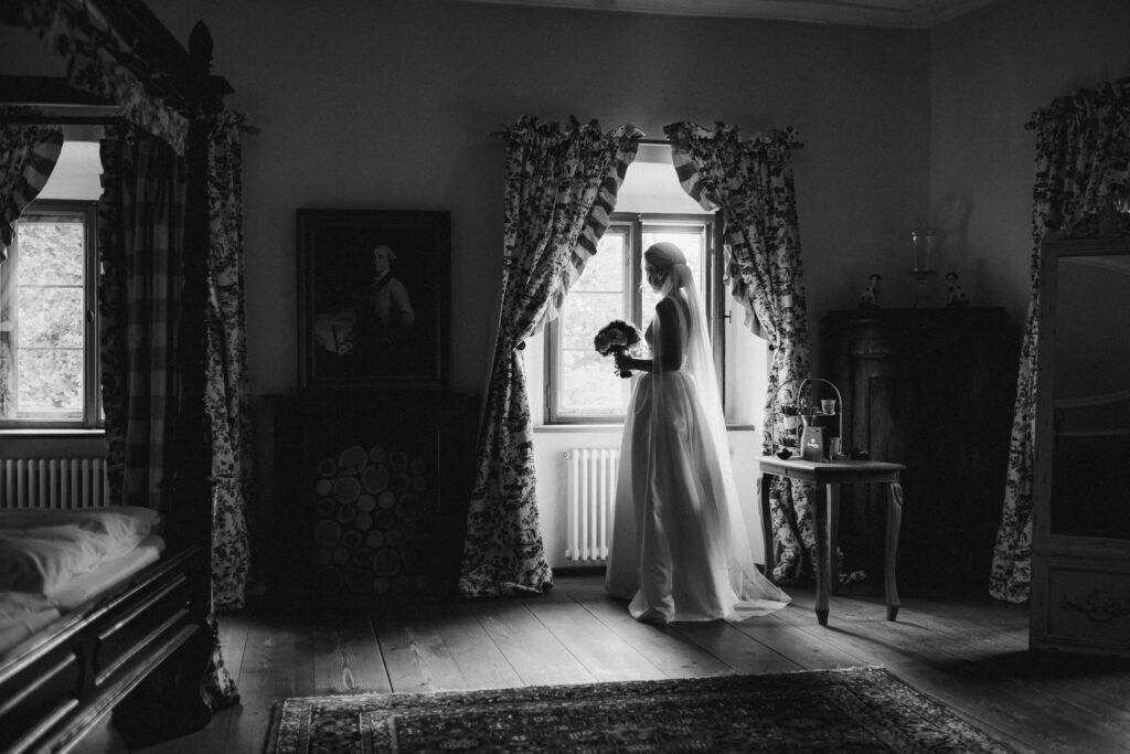 Braut steht erwartungsvoll am Fenster