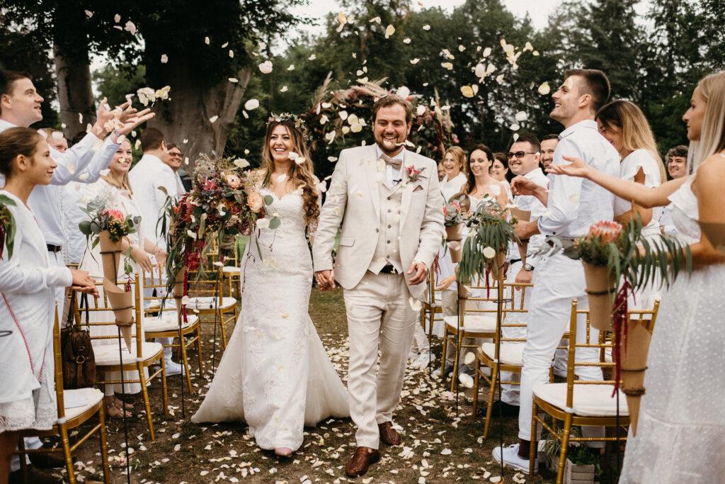 Hochzeit Schloss Reichmannsdorf Brautpaar beim Auszug nach der Zeremonie im Blumenregen